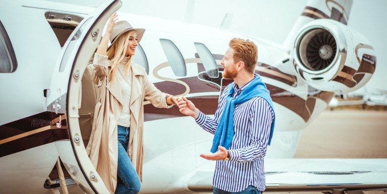 Young couple getting together in front of a private jet